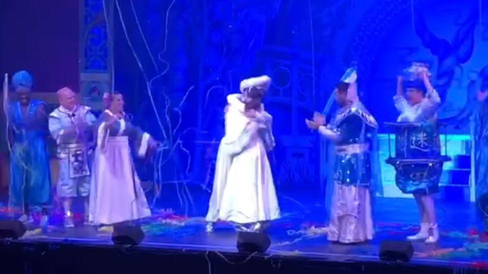 The pair hug on stage