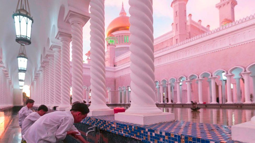 In this picture taken on April 1 2019, children perform ablutions before praying at the Sultan Omar Ali Saifuddien mosque in Bandar Seri Begawan