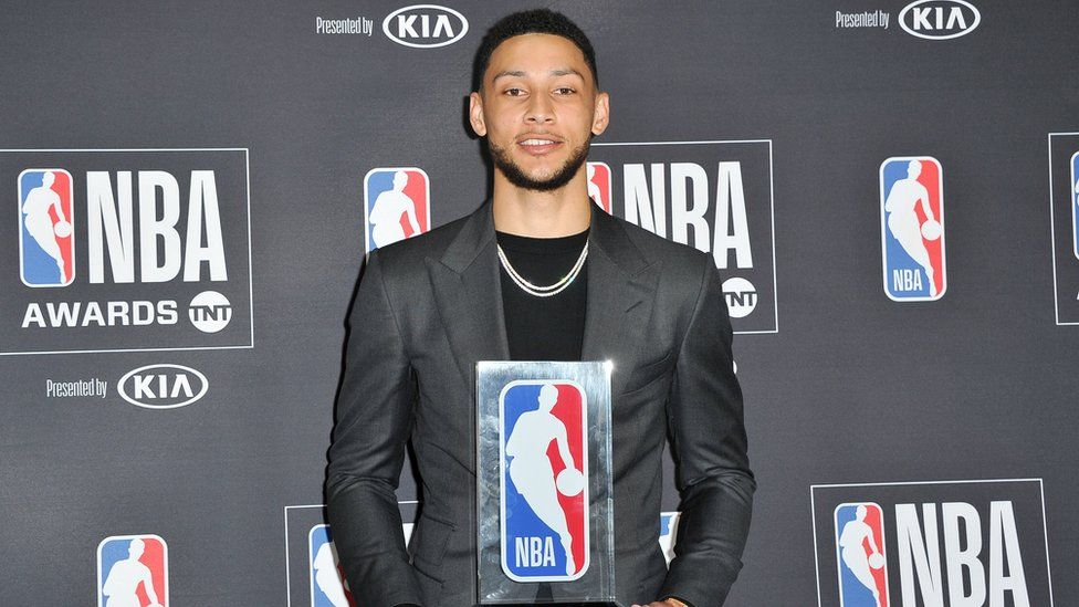 Ben Simmons poses with his 2017-2018 NBA Rookie of the Year award at a media event