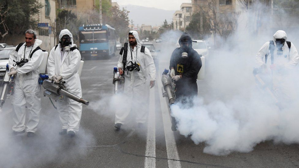 Workers disinfect a street in Tehran to prevent the spread of the Covid-19 virus (18 March 2020)