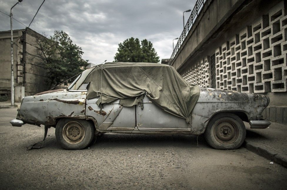 A lone Soviet era car sits in a parking lot outside the building