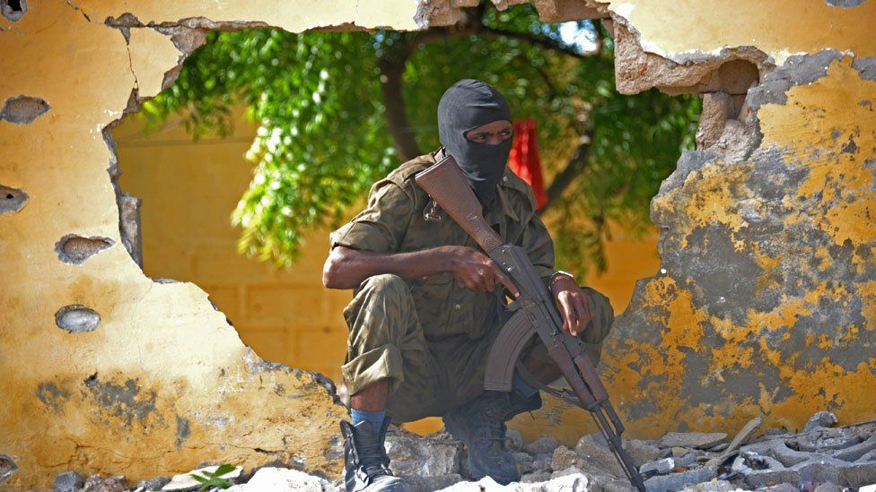 A Somali soldier stands guard next to the site where al-Shabab militants carried out a suicide attack in Mogadishu