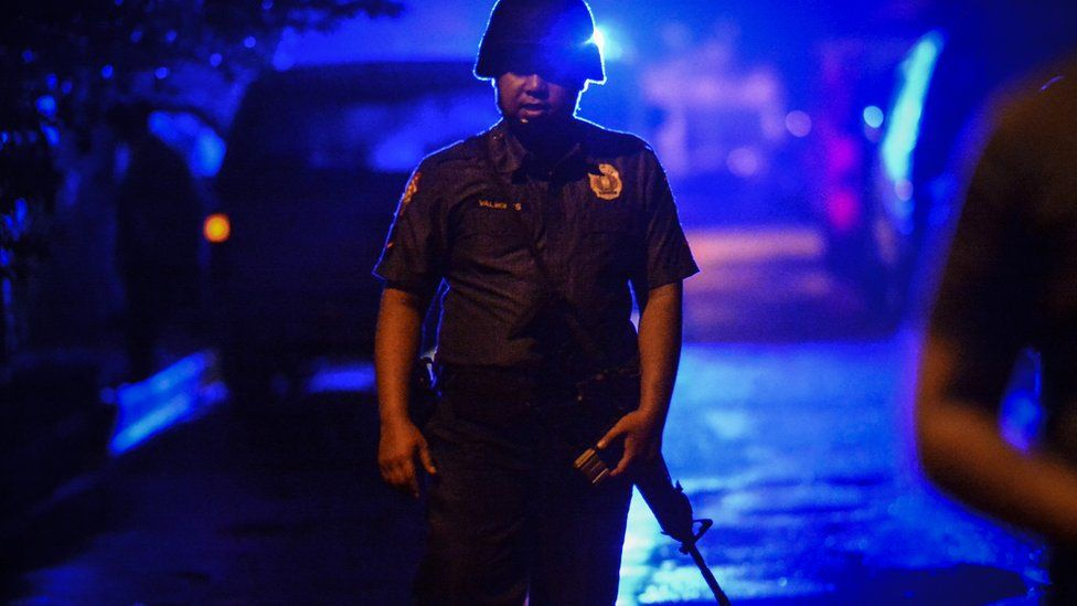 A police officer stands guard near the scene where a man was killed by unknown assailants in Quezon city, Metro Manila, Philippines