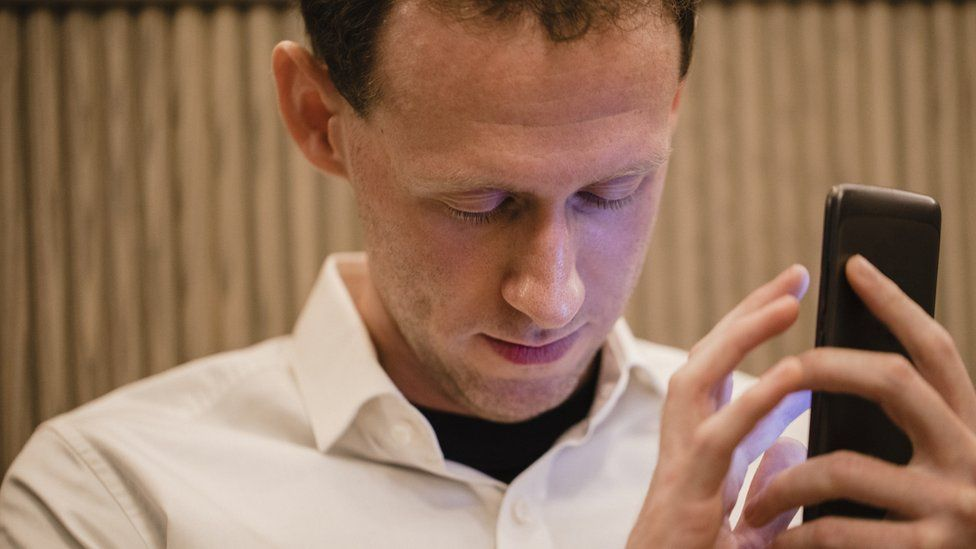 A close-up of a man wearing casual clothing, he has his smartphone in his hand and he is using a visually impaired mobile app to help assist him