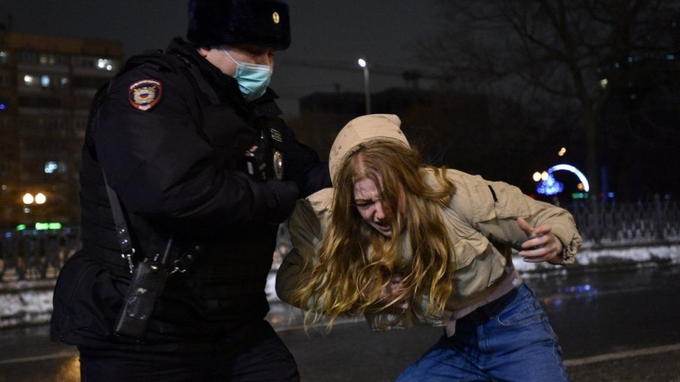 A law enforcement officer detains a woman who is bent over at Moscow protest