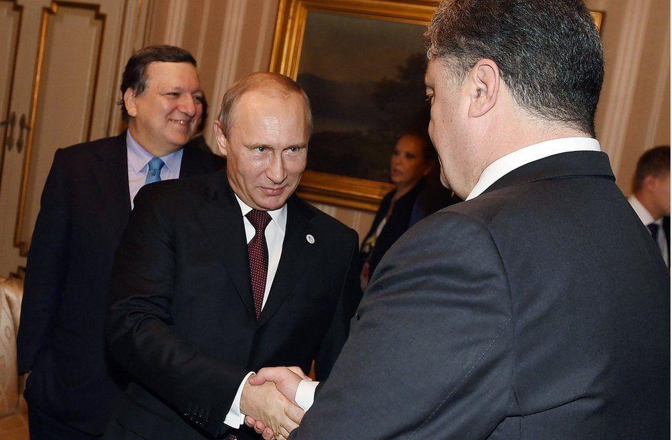Russia's President Vladimir Putin (C) shakes hands with Ukraine's President Petro Poroshenko before their meeting with European leaders on Ukraine's crisis, on October 17, 2014