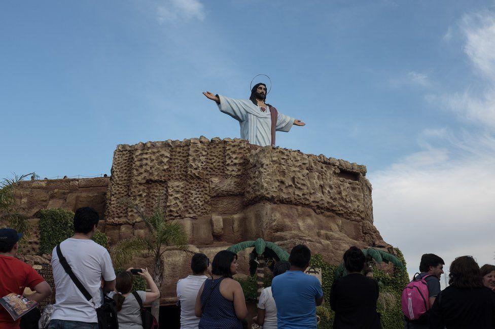 Tourists watch Jesus rise
