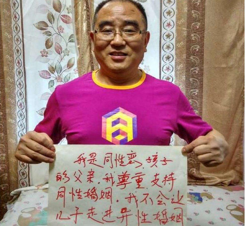 Picture of Chinese parent holding up a sign declaring they would not pressure their children into marriage.