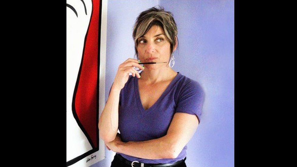 Ellen Forney posing with a paintbrush in hand