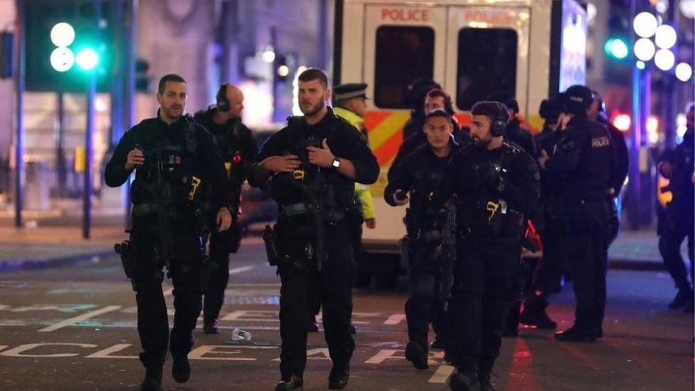 Armed police patrol along Oxford street