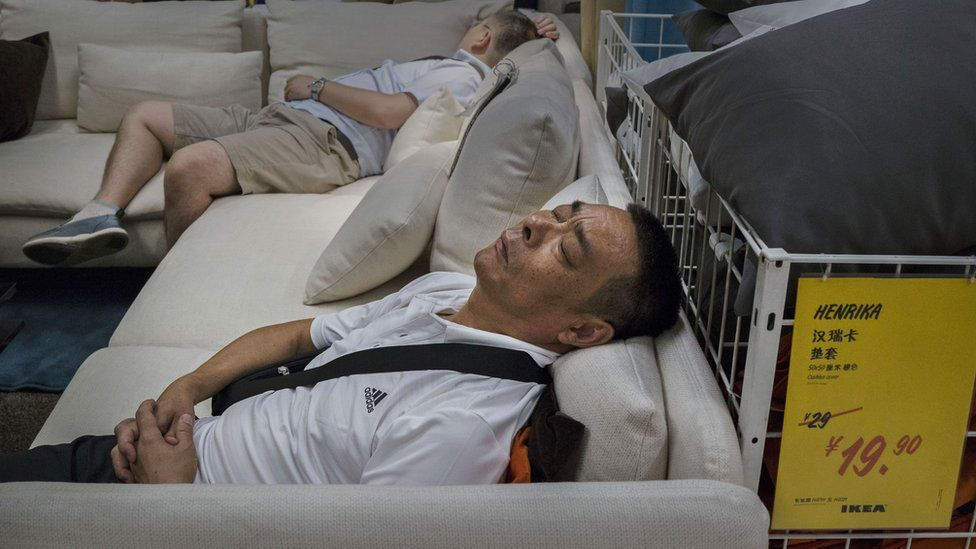 Chinese shoppers sleep on a sofa in an Ikea showroom