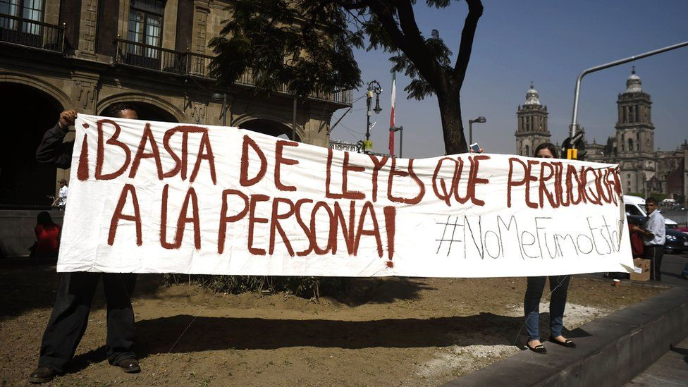 """Demonstrators holding banner saying """"Enough of laws which are detrimental to people"""""""