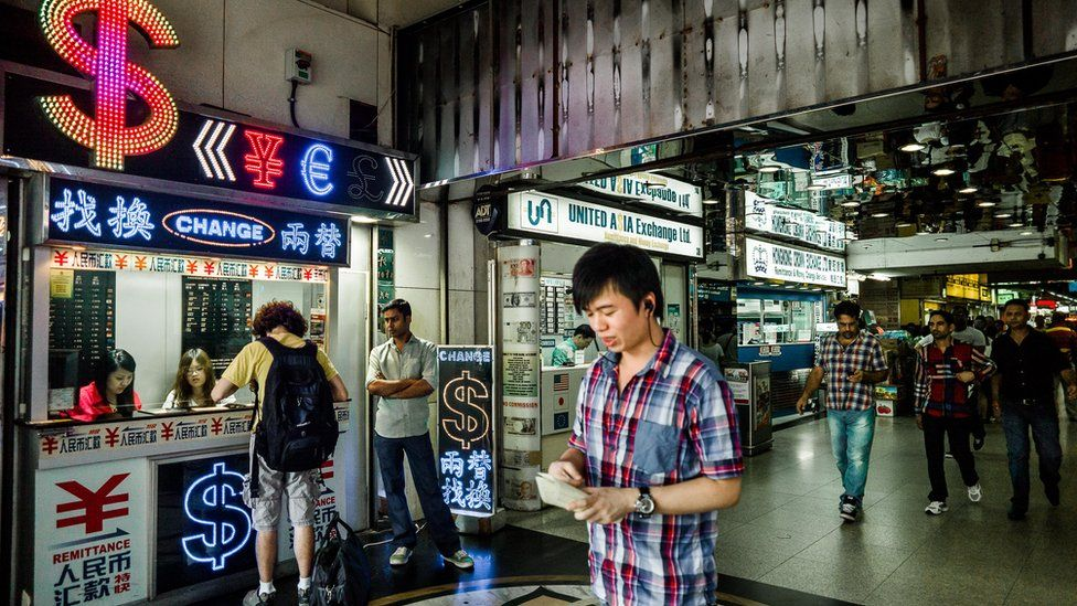 File photo: A man walks past a currency exchange booth in Hong Kong on October 24, 2012