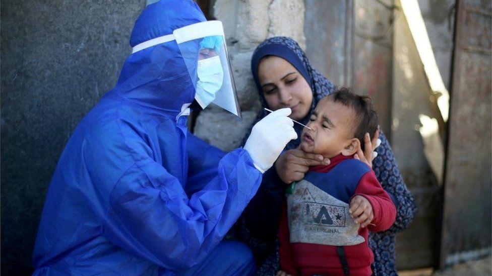 Seorang pekerja medis Palestina mengumpulkan sampel usap dari seorang anak laki-laki untuk diuji penyakit coronavirus (COVID-19), di Jalur Gaza selatan.
