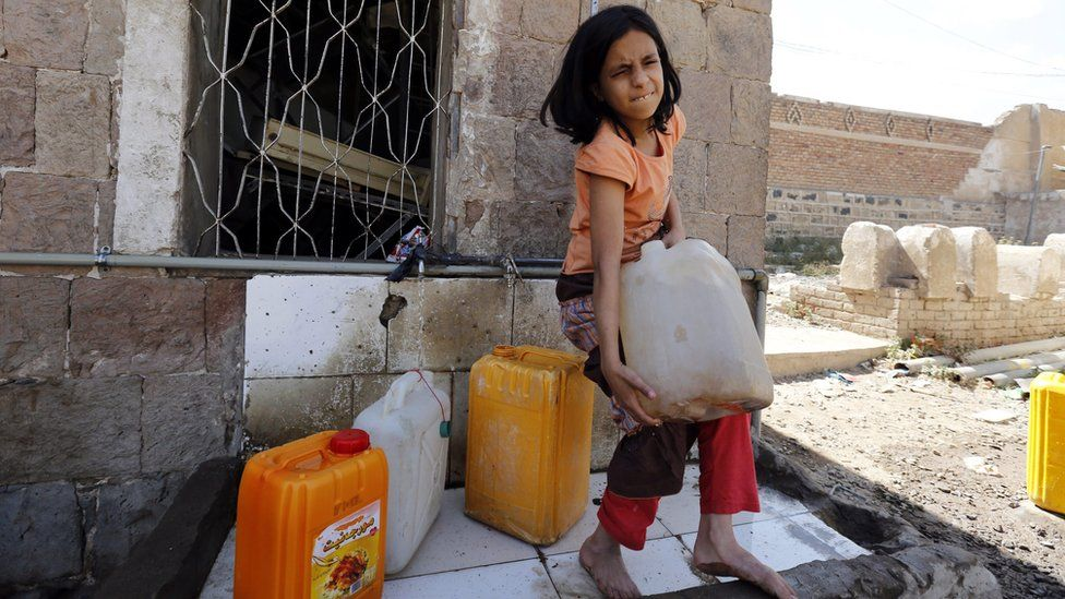 A Yemeni girl tries to carry a jerrycan full of clean water at a donated source amid ongoing widespread disruption of water supplies