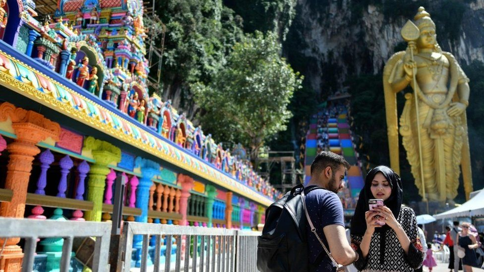 Visitors near the colourful stairs at Malaysia's Batu Caves