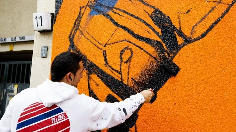 The artist Deih works on his street art painting on the outskirts of a residential house in Berlin (15 September 2017)
