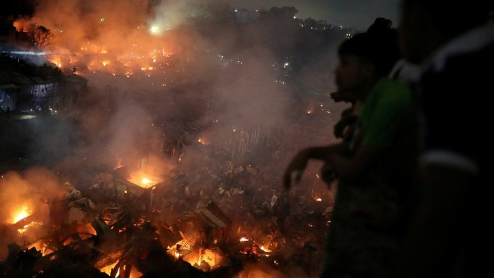 People gather at a rooftop to watch the fire that broke out at a slum in Dhaka, 16 August