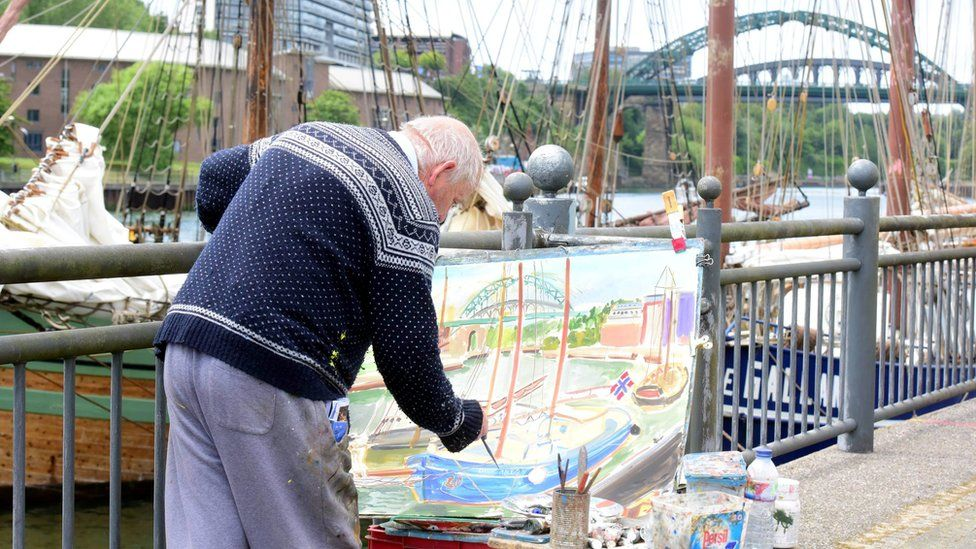 Man painting tall ship scene