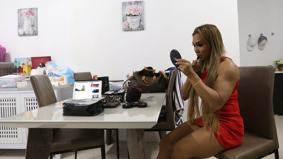 Fon sports a red dress and is seen applying make up in the picture.