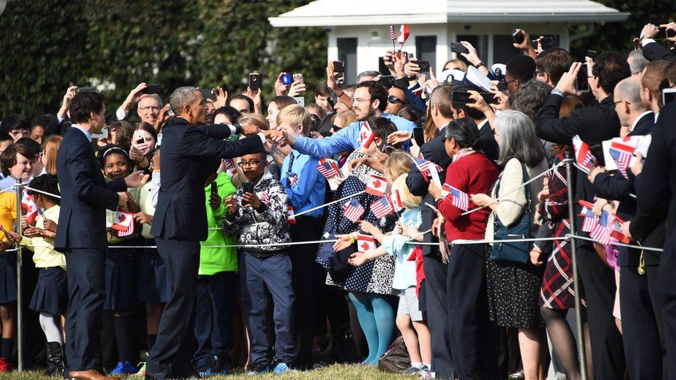 "US President Barack Obama and Canada""s Prime Minister Justin Trudeau greet the crowd during a welcome ceremony during a State Visit on the South Lawn of the White House on March 10, 2016 in Washington, DC"