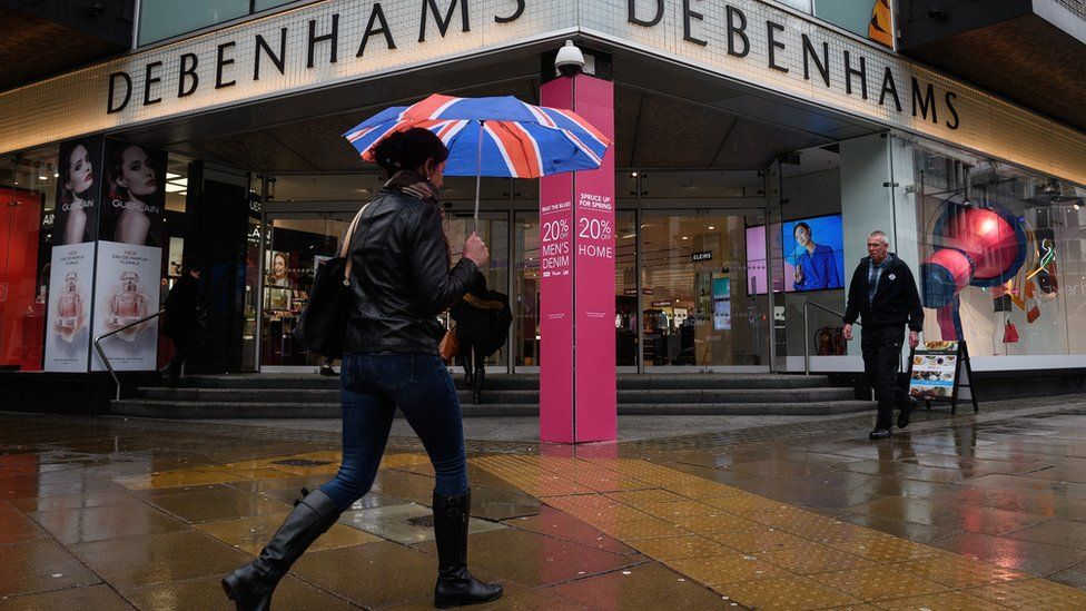 Shoppers pass a branch of the Debenhams chain of department stores on Oxford Street.
