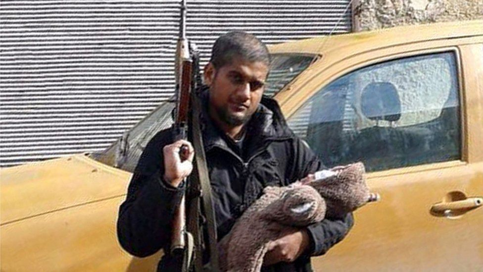 A man thought to be Siddhartha Dhar aka Abu Rumaysah holding a baby and an AK47 rifle in 2014