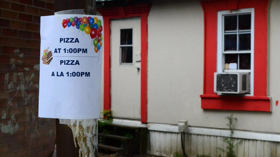 A sign indicating a pizza day at the trailer park