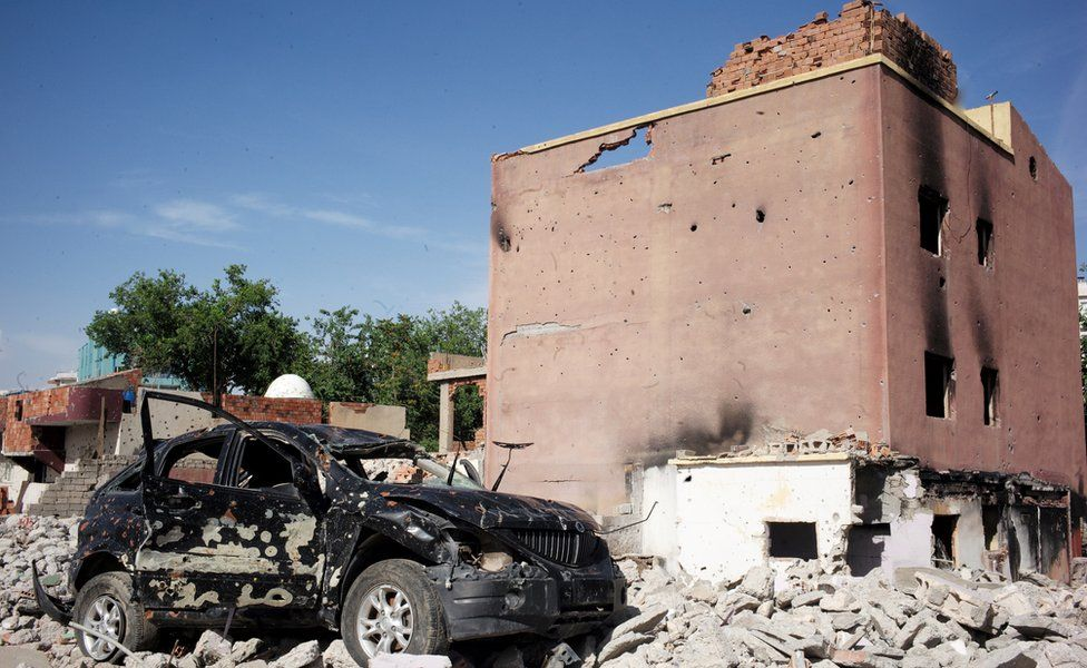 Badly damaged car and building in Cizre, Turkey - May 2016