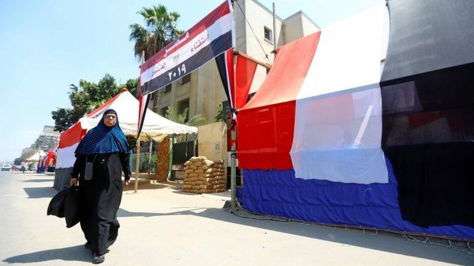 An Egyptian woman walks in front of a polling station covered from outside by Egyptian flags, during the preparations for the upcoming referendum on constitutional amendments in Cairo, Egypt on 18 April 2019