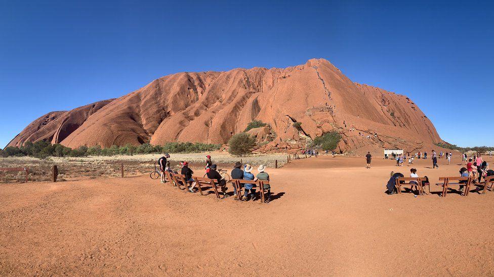 Locals watch on as tourists climb Uluru