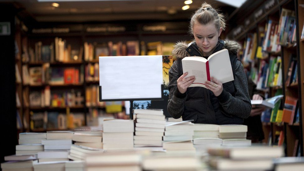 woman reading a book in book shop