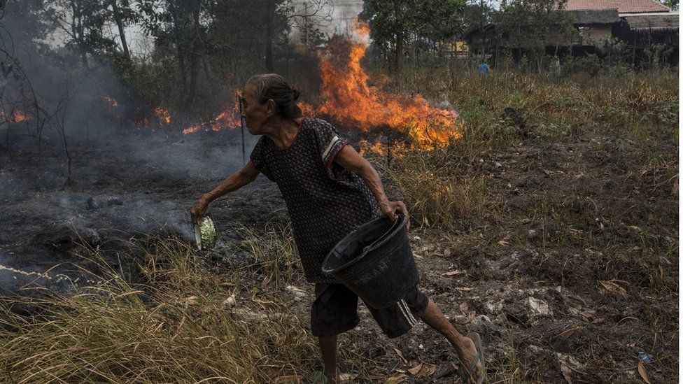 Woman fighting fire with a small bowl