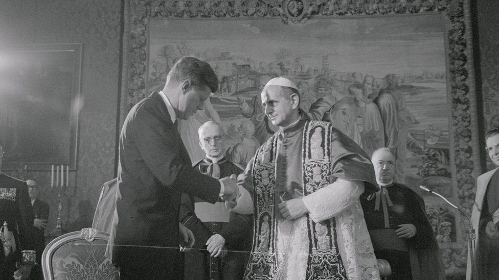 A black and white photograph, 1963, shows JFK shaking the hand of the pope, flanked by multiple high-ranking clergy amid opulent surroundings in the Vatican