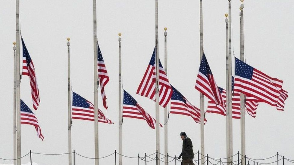 Visitors to the Washington Monument walk past flags flying a half-staff in honour of Supreme Court Justice Antonin Scalia on a wintry Presidents Day holiday in Washington, on 15 February 2016.