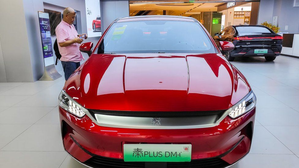 A man looks at an electric car in a BYD store in Shanghai, China.
