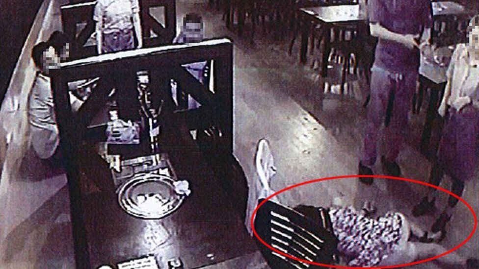 CCTV image shows customers and staff looking at the intoxicated woman on the floor