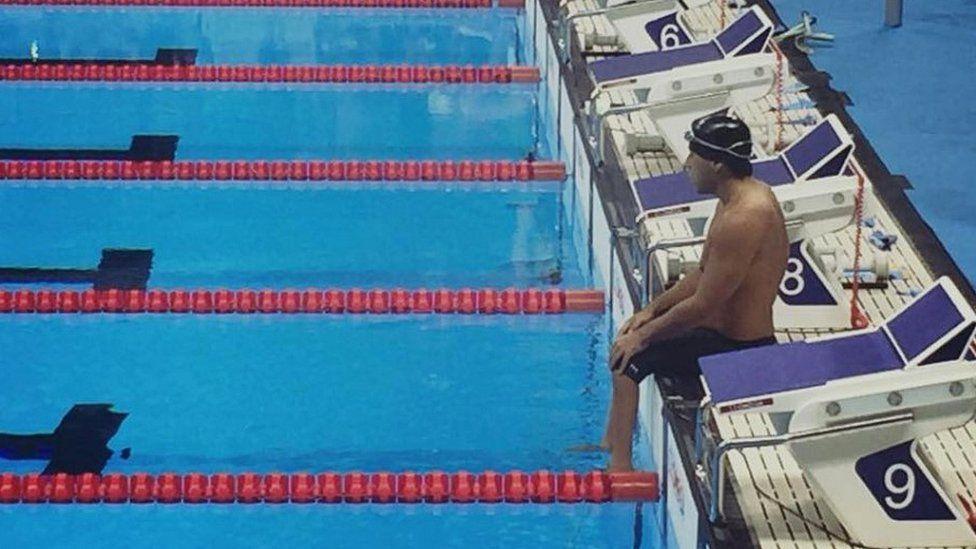 Jesus De Marchena Acevedo sitting on the poolside at Rio