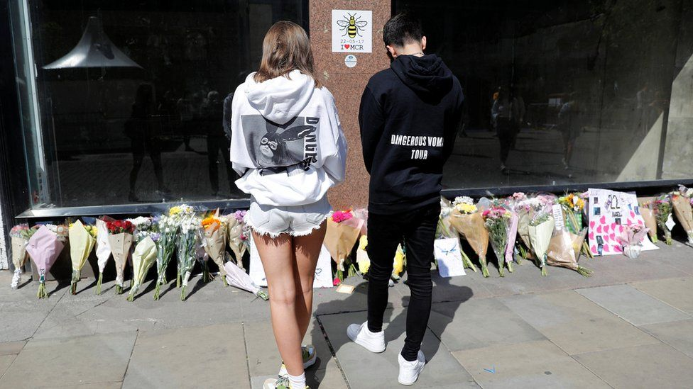 "People wearing Ariana Grande sweatshirts look at tributes left in St Anne""s Square on the first anniversary of the Manchester Arena bombing"