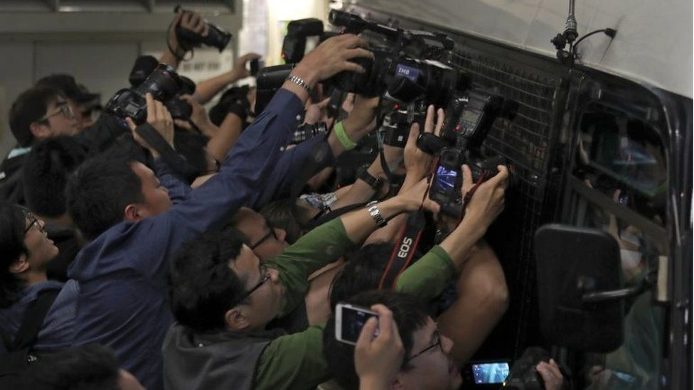 Photographers try to take pictures of Donald Tsang, former leader of Hong Kong, who is inside a prison bus leaving the high court in Hong Kong, Monday, Feb. 20, 2017.