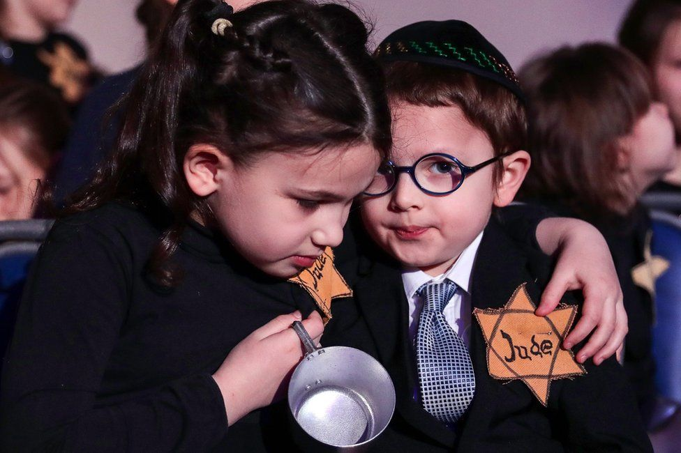 Children take part in a memorial ceremony for Holocaust victims
