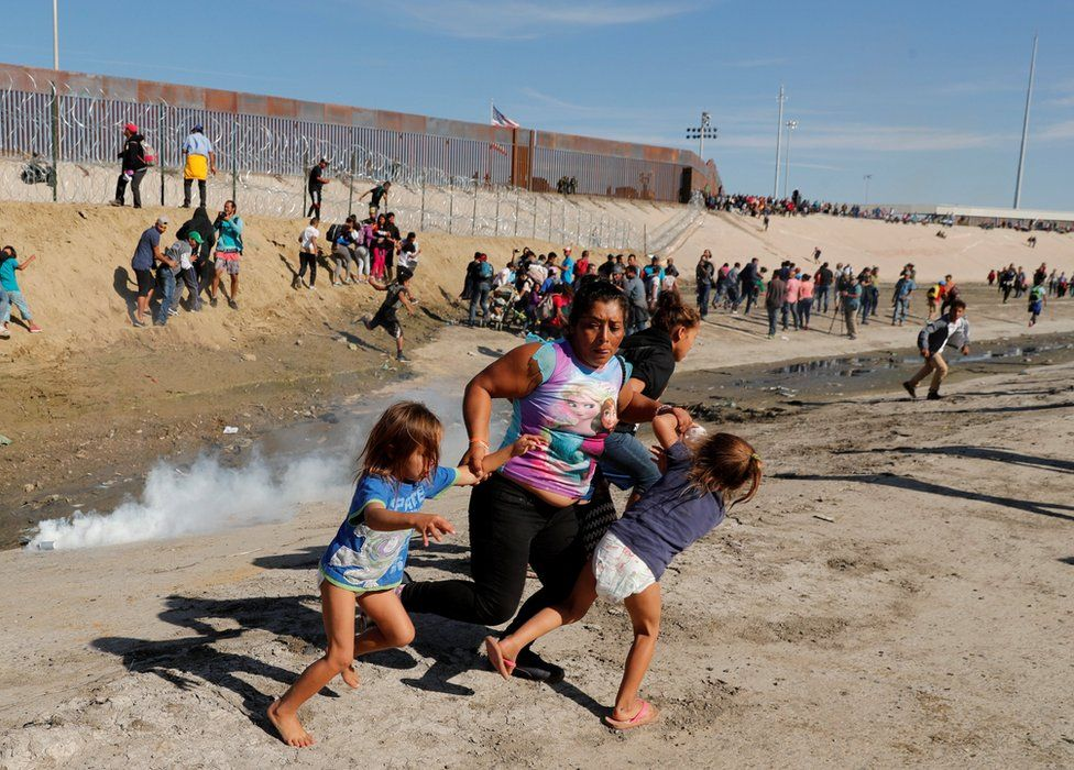 A woman runs from tear gas holding two of her children