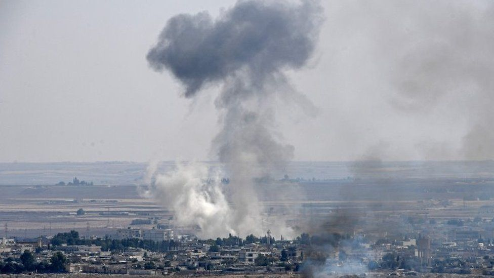 Smoke rises from the Syrian town of Ras al-Ain, from the Turkish side of the border