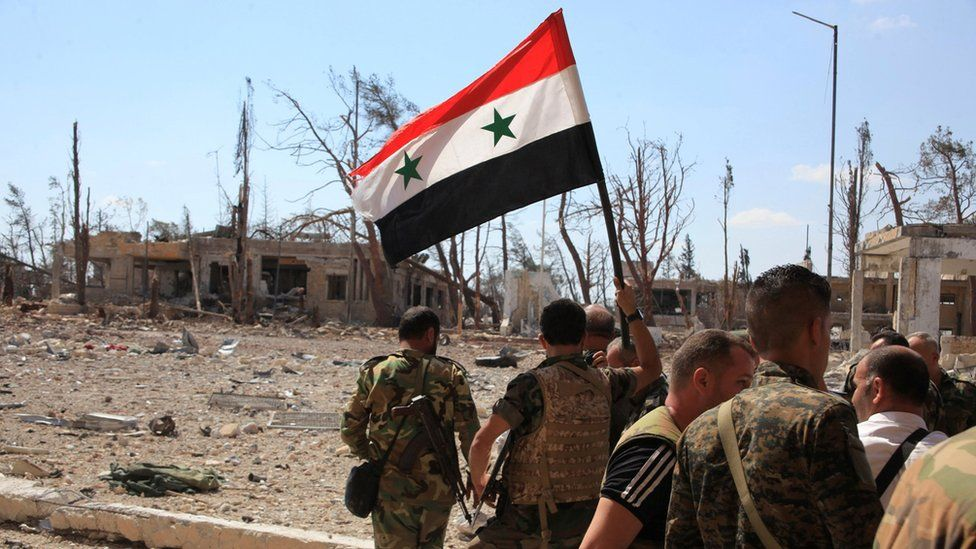 Forces loyal to Syrian President Bashar al-Assad hold up a Syrian flag as they walk through a recaptured military complex in Aleppo (5 September 2016)