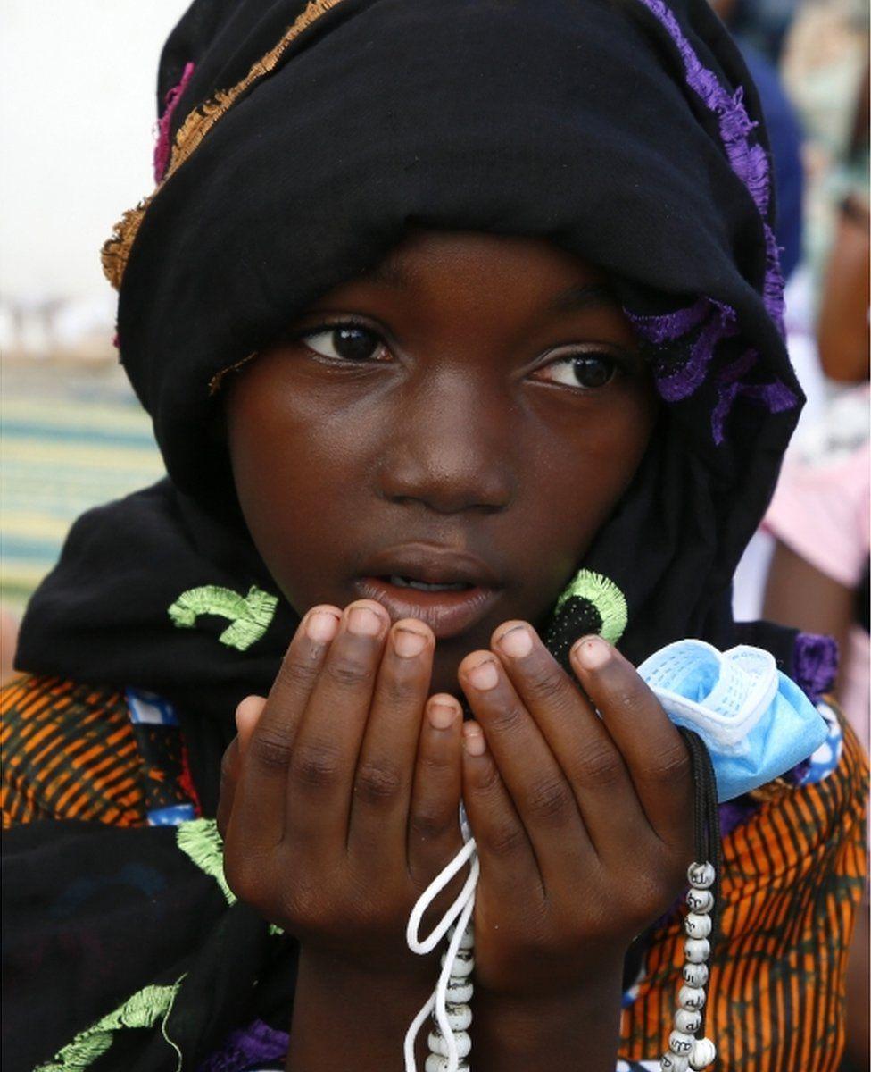 A girl holds prayer beads in her hands as she prays...
