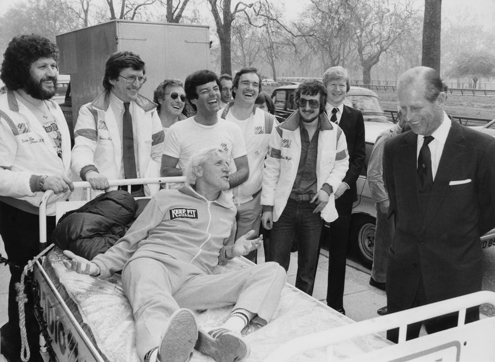 Jimmy Savile talking to the Duke of Edinburgh in 1981 while other Radio 1 djs look on