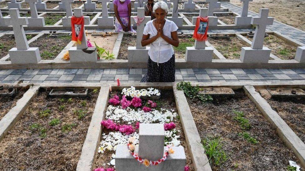 Relatives pay their respects outside St Sebastian's Church