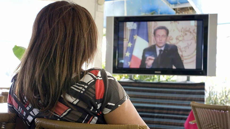 A woman in Guadeloupe watches former French President Nicolas Sarkozy on TV in 2009