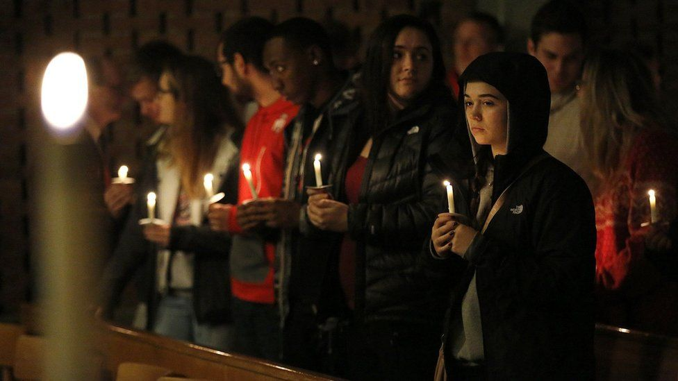 Guests stand for a moment after lighting their candles during a vigil at St Stephen's Episcopal Church in Columbus, Ohio
