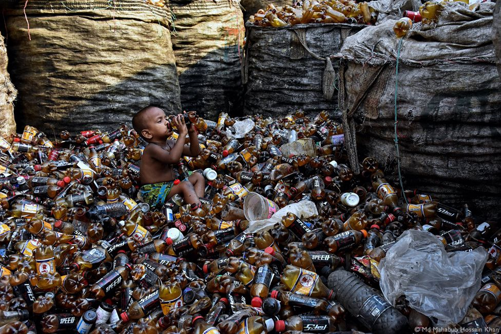 Child surrounded by plastic bottles